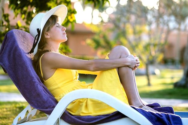 Mujer joven que se relaja al aire libre en un día soleado de verano. señora feliz que se acuesta en la silla de playa cómoda que sueña despierto pensando. calma hermosa niña sonriente disfrutando de aire fresco relajante con los ojos cerrados.