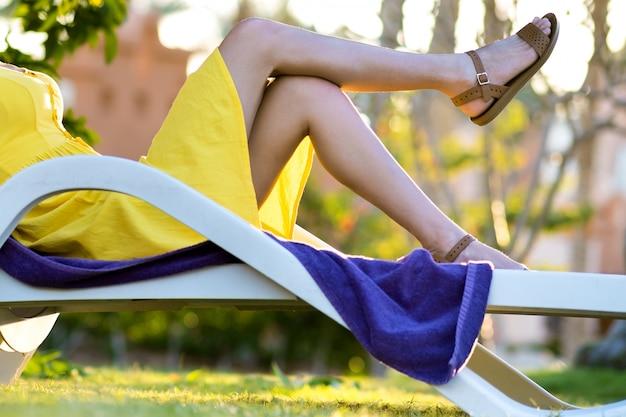 Mujer joven que se relaja al aire libre en un día soleado de verano. señora feliz que se acuesta en la silla de playa cómoda que sueña despierto pensando.
