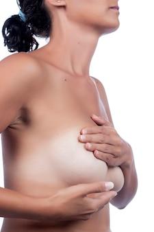 Mujer joven que revisa la mama (autoexamen) en busca de anomalías, nódulos o bultos extraños para el cáncer de mama.