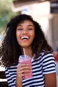 Mujer joven que ríe con la bebida del smoothie