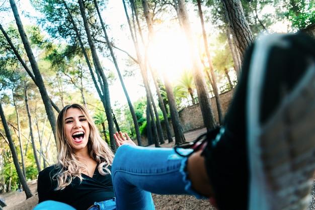 Mujer joven que ríe con una broma que se sienta en un parque.