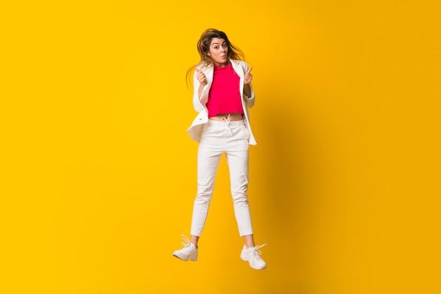 Mujer joven que salta sobre la pared amarilla aislada que hace gesto de la victoria
