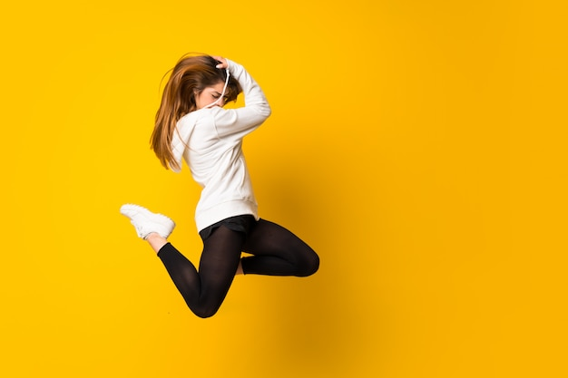 Mujer joven que salta sobre la pared amarilla aislada