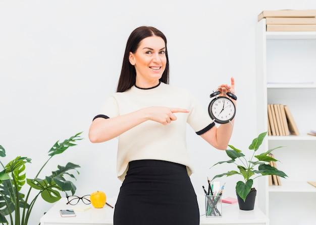 Mujer joven que señala el dedo en el reloj en oficina