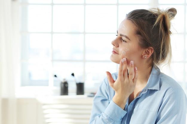 Mujer joven que se separa la crema facial. concepto de cuidado de la piel.