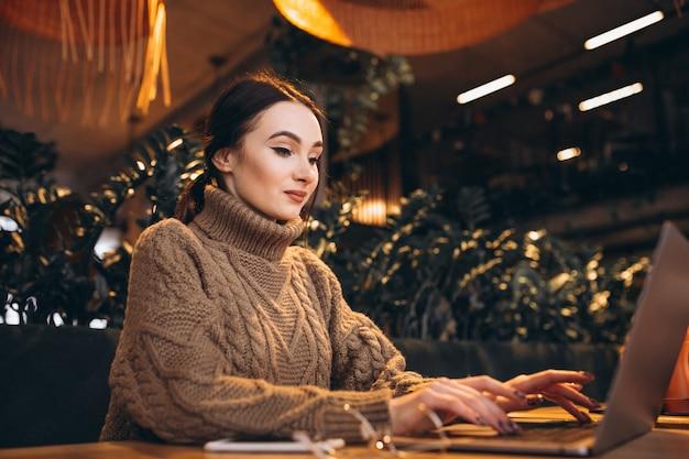 Mujer joven que se sienta en café y que trabaja en la computadora portátil