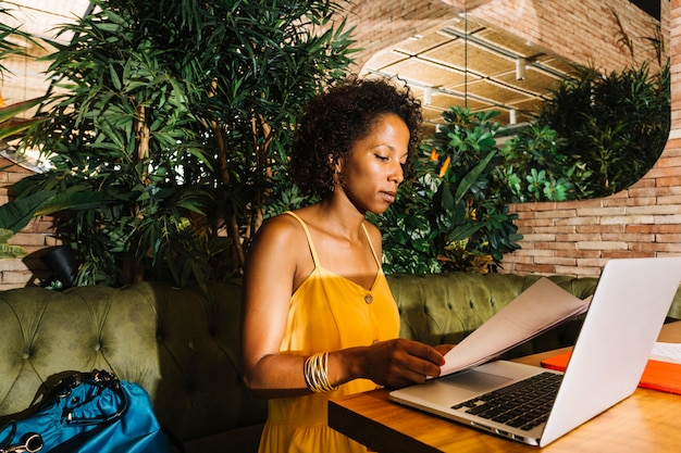 Mujer joven que se sienta en el documento de la lectura del restaurante con el ordenador portátil en la tabla de madera
