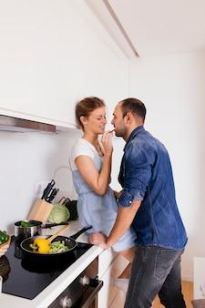 Mujer joven que se sienta en la ensalada de alimentación de contador de cocina a su marido
