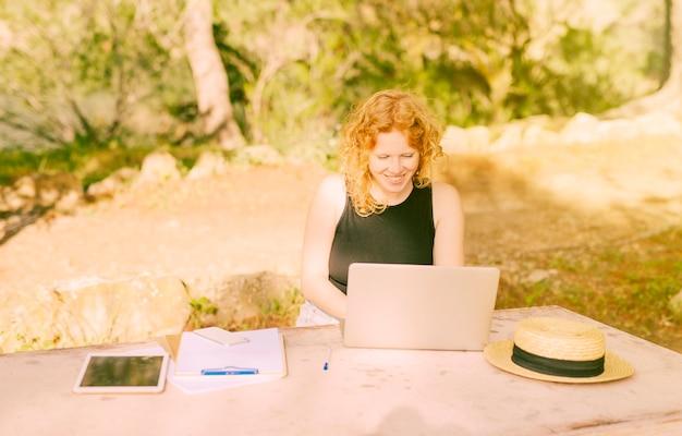 Mujer joven que se sienta en el escritorio afuera y que trabaja en la computadora portátil