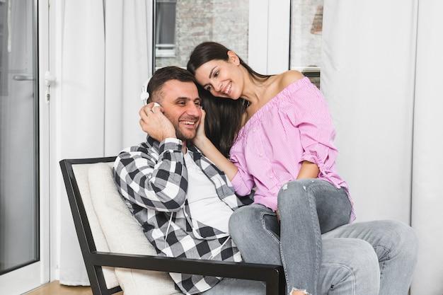 Mujer joven que se sienta en la música que escucha del regazo de su novio en el auricular
