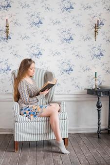 Mujer joven que se sienta en la silla del brazo contra el libro de lectura del papel pintado