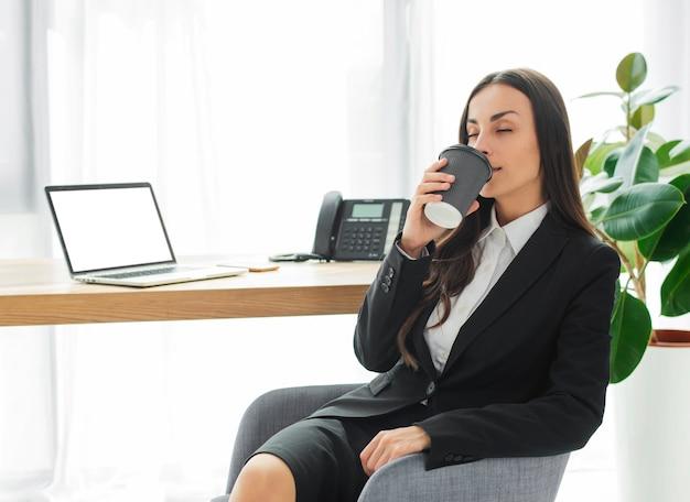 Mujer joven que se sienta en silla en el escritorio de oficina que goza del café