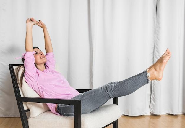 Mujer joven que se sienta en la silla que estira sus manos y piernas