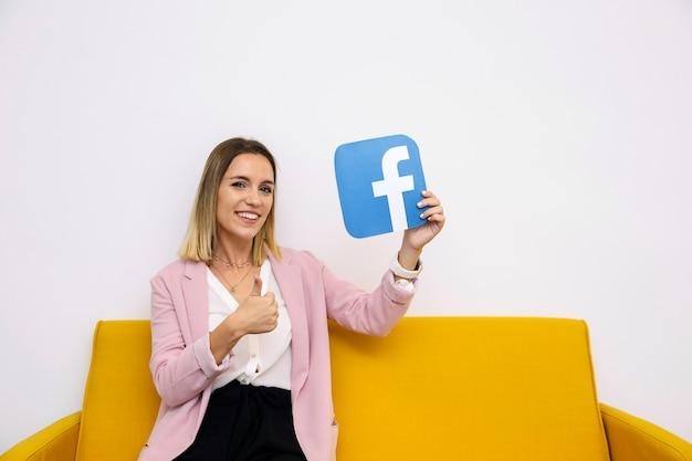 Mujer joven que se sienta en el sofá amarillo que lleva a cabo el icono de facebook que muestra la muestra del thumbup