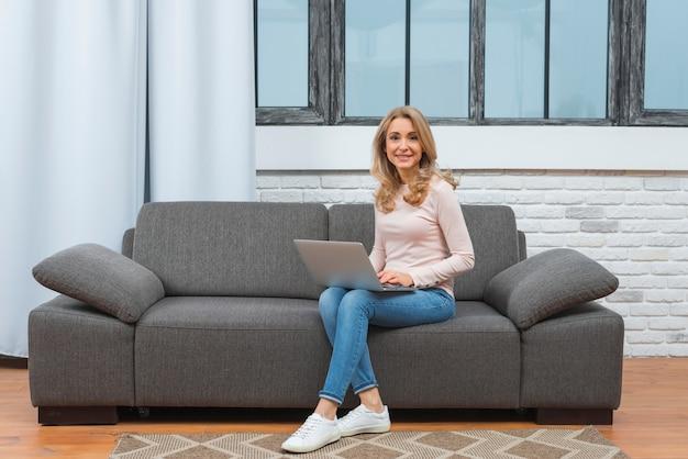 Mujer joven que se sienta en el sofá usando la computadora portátil que mira la cámara