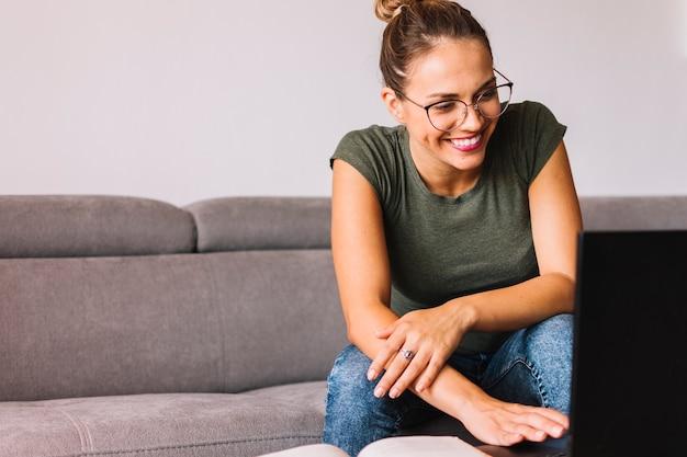 Mujer joven que se sienta en el sofá usando la computadora portátil