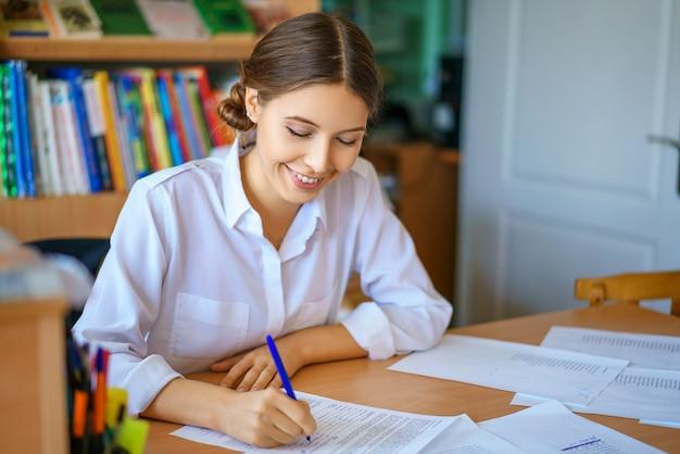 Mujer joven que se sienta en la tabla en la camisa blanca y los papeles de firma, concepto del negocio.