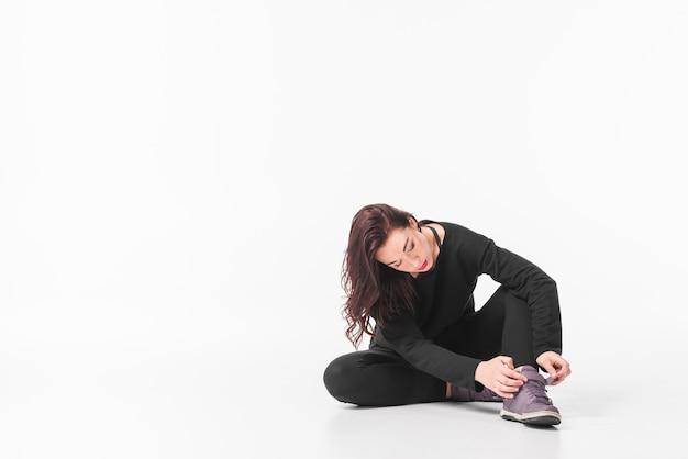 Mujer joven que se sienta en la tierra que pone la correa del zapato contra el fondo blanco