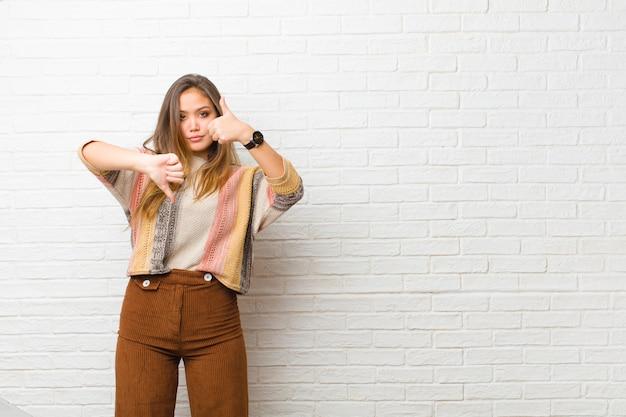 Mujer joven que se siente confundida, despistada e insegura, sopesando lo bueno y lo malo en diferentes opciones u opciones en la pared de ladrillo