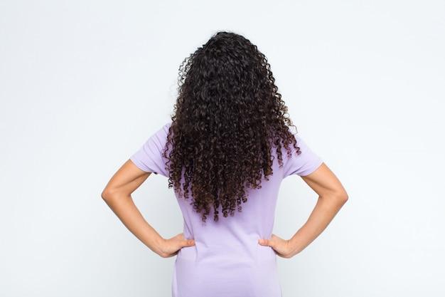 Mujer joven que se siente confundida o llena o dudas y preguntas, preguntándose, con las manos en las caderas, vista posterior sobre la pared blanca