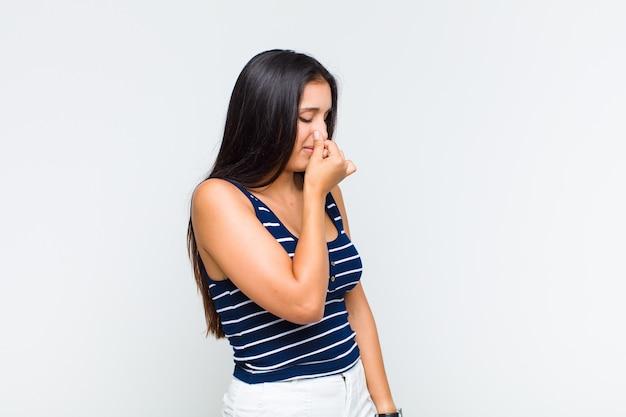 Mujer joven que se siente disgustada, tapándose la nariz para evitar oler un hedor desagradable y desagradable