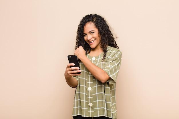 Mujer joven que se siente feliz, positiva y exitosa, motivada cuando enfrenta un desafío o celebra buenos resultados con un teléfono inteligente