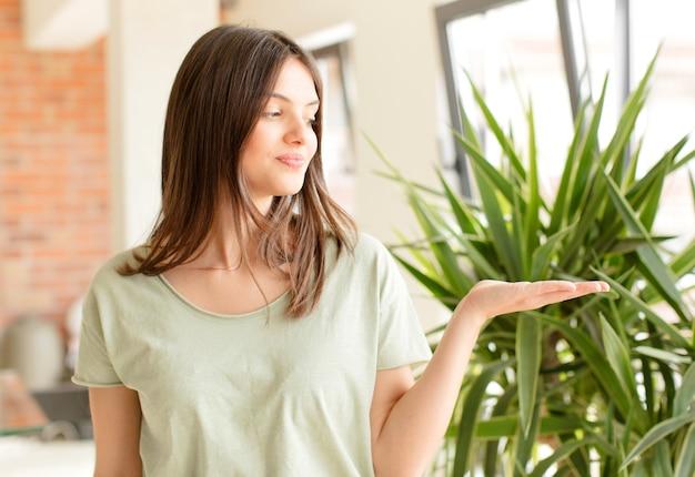 Mujer joven que se siente feliz y sonriendo casualmente mirando a un objeto o concepto sostenido en la mano al costado