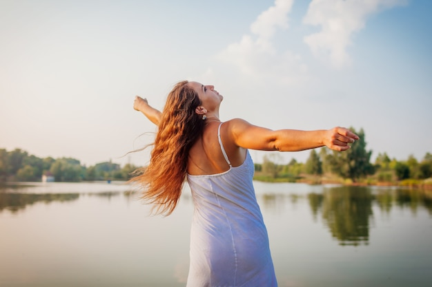 Mujer joven que se siente libre y feliz levantando los brazos y dando vueltas por el río de verano