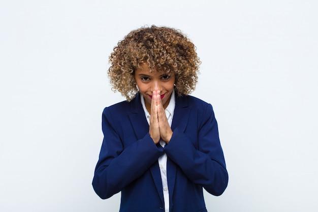 Mujer joven que se siente preocupada, esperanzada y religiosa, rezando fielmente con las palmas presionadas, pidiendo perdón contra la pared