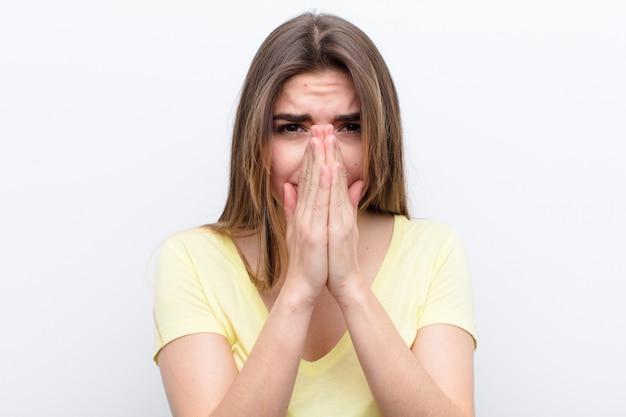 Mujer joven que se siente preocupada, esperanzada y religiosa, rezando fielmente con las palmas presionadas, pidiendo perdón