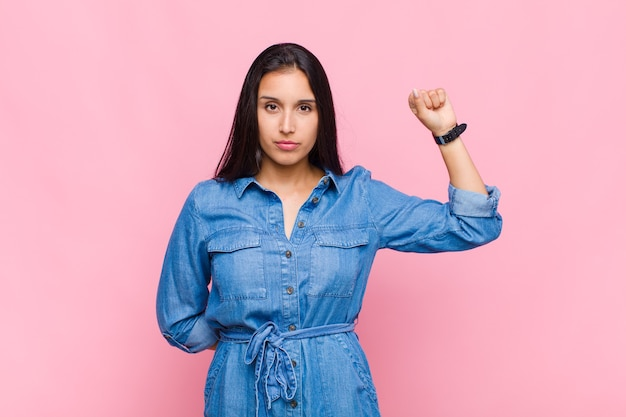 Mujer joven que se siente seria, fuerte y rebelde, levanta el puño, protesta o lucha por la revolución