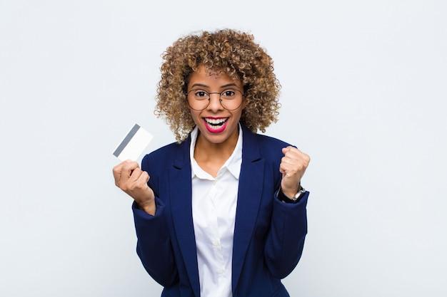 Mujer joven que se siente sorprendida, emocionada y feliz, riendo y celebrando el éxito, diciendo ¡guau! con una tarjeta de crédito