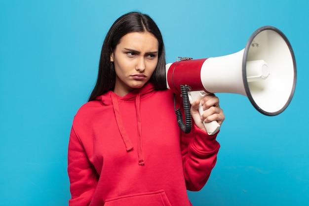 Mujer joven que se siente triste, molesta o enojada y mira hacia un lado con una actitud negativa, frunciendo el ceño en desacuerdo
