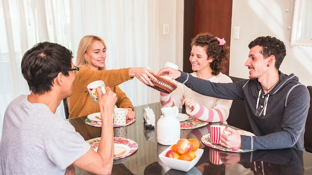 Mujer joven que sirve comida a sus amigos desayunando juntos
