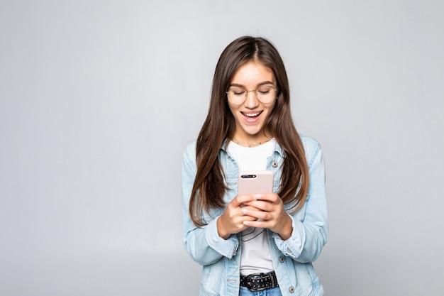 Mujer joven que sonríe y que manda un sms en su teléfono móvil, aislado sobre la pared blanca.