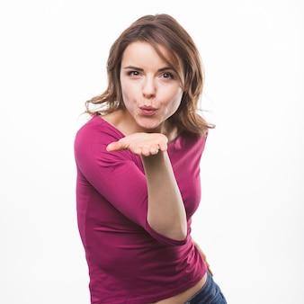 Mujer joven que sopla beso volador sobre fondo blanco