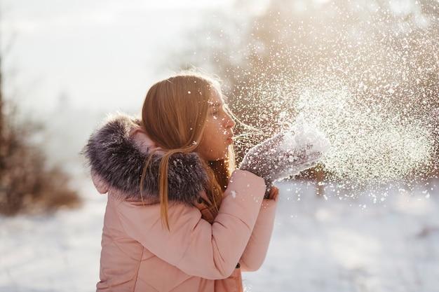 Mujer joven que sopla nieve de las manos