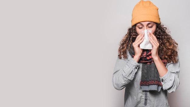 Mujer joven que sopla su nariz con papel de seda sobre fondo gris