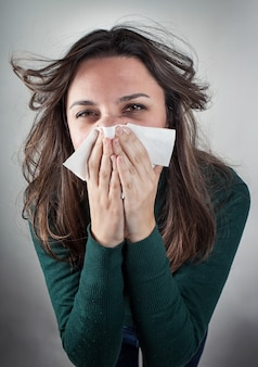 Mujer joven que sopla su nariz con el papel de papel.