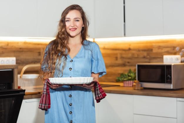 Mujer joven que sostiene la bandeja de la hornada con los dulces o la carne deliciosos. interior de cocina doméstica. mujer tomando bandeja para hornear. concepto de cocina casera.