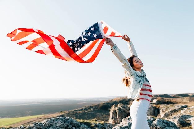 Mujer joven que sostiene la bandera estadounidense en la cima de la montaña