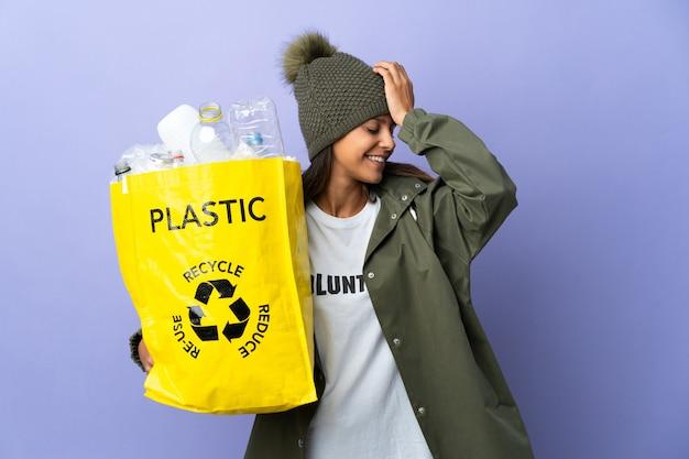 Mujer joven que sostiene una bolsa llena de plástico se ha dado cuenta de algo y tiene la intención de la solución