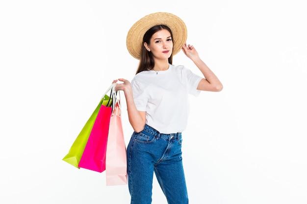 Mujer joven que sostiene bolsos coloridos aislados en la pared blanca