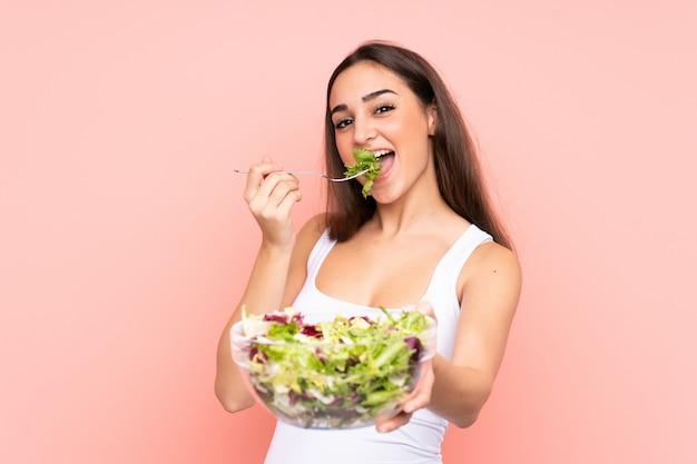 Mujer joven que sostiene una ensalada aislada en la pared rosada