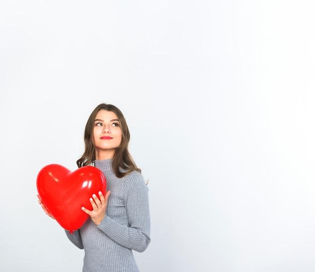 Mujer joven que sostiene el globo rojo del corazón en manos