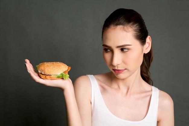 Mujer joven que sostiene la hamburguesa en fondo gris