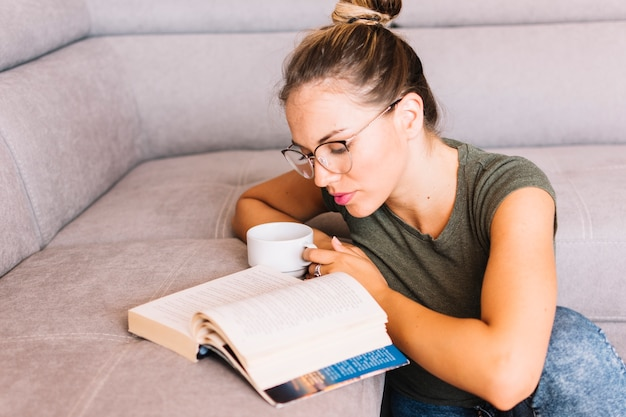 Mujer joven que sostiene el libro de lectura de la taza de café