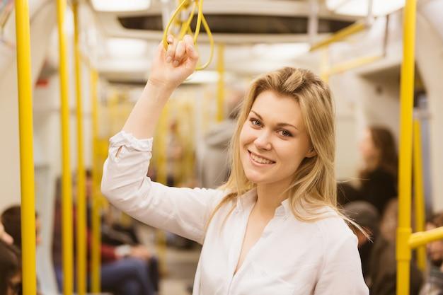 Mujer joven que se sostiene con la mano derecha dentro del tubo de londres.