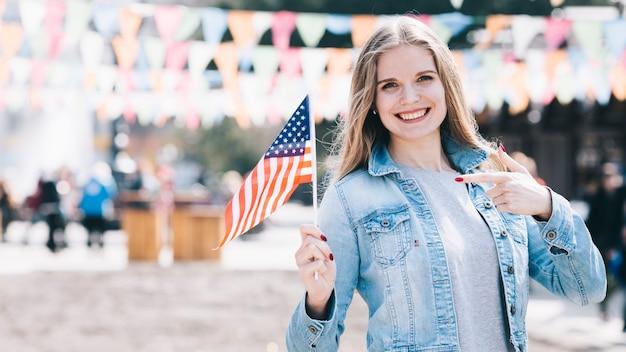 Mujer joven que sostiene la pequeña bandera de estados unidos