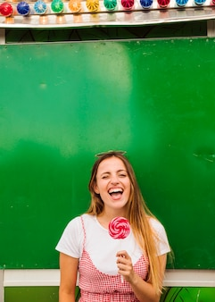 Mujer joven que sostiene la piruleta roja en su mano que ríe